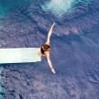 Girl standing on springboard, preparing to dive — Stock Photo #24306645