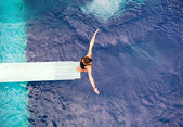 Girl standing on springboard, preparing to dive — Stock Photo
