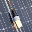 Energy saving light bulb on the solar panel - Stock Photo