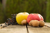 Apples on wooden table over autumn bokeh background — Foto Stock