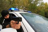 Masked policeman shoots from police car — Stock Photo