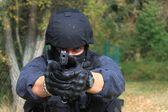 Masked policeman shoots — Stock Photo