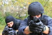 Masked policeman shoots — Stock Photo