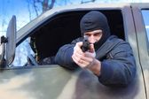 Assassin shooting from a moving car — Stock Photo