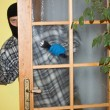 Burglar in mask breaking into a house through door, with gun — Stock Photo