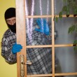 Burglar in mask breaking into a house through door, with gun — Stockfoto