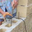 Bricklayer builds a wall, rebar cutting angle grinder — Stock Photo