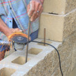 Bricklayer builds a wall, rebar cutting angle grinder - Stock Photo
