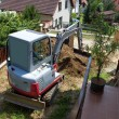 A small excavator provides garden at the house — Stock Photo