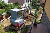 Uma escavadeira pequena fornece jardim em casa — Fotografia Stock