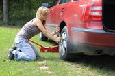 Young blond girl puncture repairs — Stock Photo