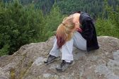 Sad teenager sitting on the rocks — Stock Photo