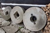 Old millstones leaning on the wooden wall of the house — Stock Photo