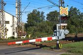 Railroad crossing with a barrier on the outskirts of Tisnov Czech Republic, the alarm sounds and a red light. — Stock Photo