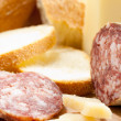Cutting board with bread, cheese and salami — Stockfoto
