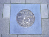 Coin of twenty-five cents in pavement — Stock Photo
