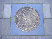 Coin of one guilder in pavement — Stock Photo