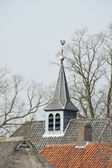 Rooftops with belfry and weathercock — Stock Photo