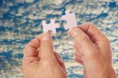 Hands connect puzzle pieces against clouds — Foto Stock
