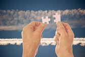 Hands connect puzzle pieces agains vapor trails — Stockfoto