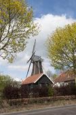 Wooden wind mill in a farm scenery — Stock Photo