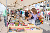 Market booth with second hand books and shopping people — Stock Photo