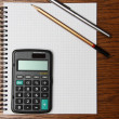 Pen, pencil and calculator on a notepad — Stock Photo