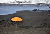 Orange umbrella on the beach — Stock Photo