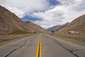 Lonely road surrounded by mountains — Stock Photo