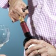 A man uncorking a bottle of red wine — Stock Photo