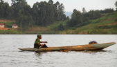 African Man Paddles Dugout Canoe — Stock Photo