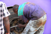 Ugandan Man Puts On a Bus Tire — Stockfoto