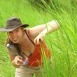 Adventure Woman Hides in Grass pretending to be an Animal — Stock Photo