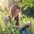 Beautiful girl reading a book on a meadow — Stock Photo