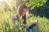Beautiful girl reading a book on a meadow — Foto Stock