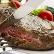 Juicy steak with fork and knife — Stock Photo #23855077