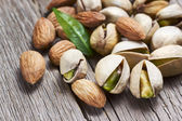 Almonds and pistachios with leaf — Stock Photo