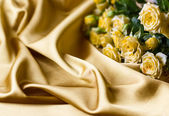 Yellow roses on silk background — Stock Photo
