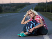 Woman with haversack sitting on the road — Stock Photo