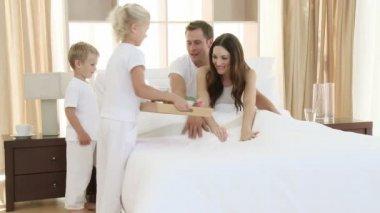 Children giving breakfast to their parents in bedroom — Stock Video