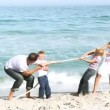 Parents and children playing with a string on the beach — Video