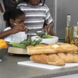 Panorama of Afro-American family making a salad at home — Video