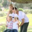 Family swinging in a park — Video