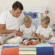 Father reading with his children in the bedroom — Stock Video