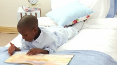 Afro-American smiling little boy reading in bed — Stock Video