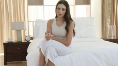 Sad woman holding a negative pregnancy test and sitting on the bed. Footage in high definition — Video Stock