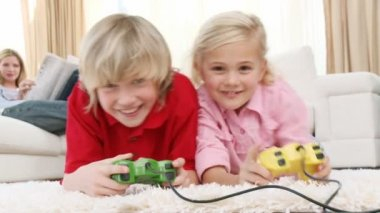 Children playing video games and parents on sofa — Stock Video #22640815