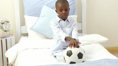 Afro-American little kid playing with a soccer ball in his bedroom — Stock Video