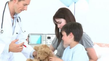 Doctor playing with a little boy recovering in hospital and his teddy bear — Stock Video
