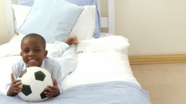 Panorama of Afro-American little kid playing with a soccer ball in hid bedroom — Stock Video